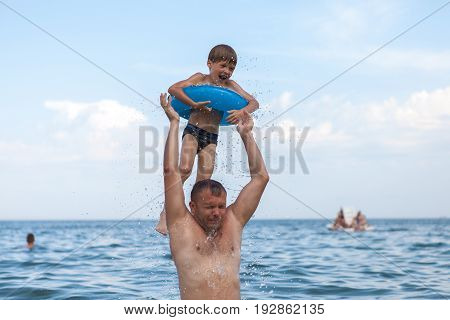 Dad and son bathe in the sea play fun.