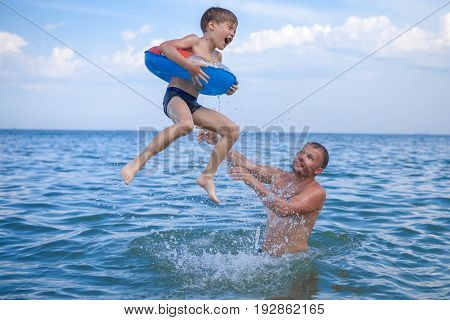 Dad And Son Bathe In The Sea, Play Fun. Dad Throws His Son Into The Water.