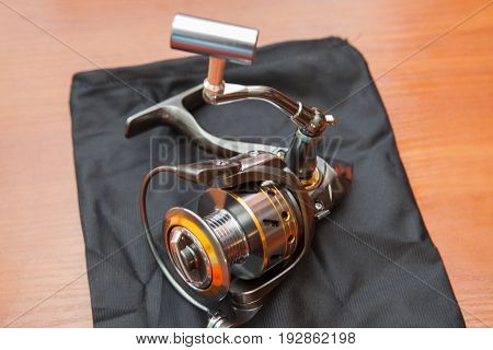 Reel For Fishing Rods, Close Up On Wood Background. Fishing Coil Close-up.