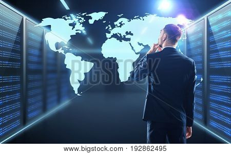 business, people and technology concept - businessman with virtual world map projection over server room background