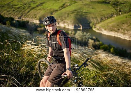 Portrait of the young cyclist standing on the hill with bike above river. Sportsman dressed in the black sportwear, with helmet and backpack. Beautiful landscape like a background. Concept of the healthy and active lifestyle