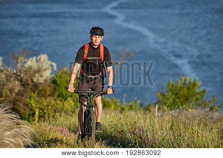 Portrait of the young cyclist riding mountain bike uphill above beautiful blue river. Sportsman dressed in the black sportwear, with helmet and backpack. Beautiful summer landscape like a background. Concept of the healthy lifestyle.
