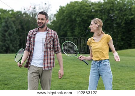 Happy Caucasian Couple With Badminton Racquets Standing Together In Park
