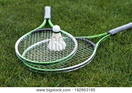 Close Up Of Shuttlecock On Badminton Rackets Lying On Green Grass