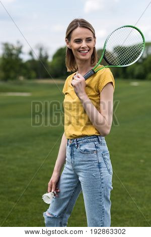 Smiling Woman Holding Badminton Racquet And Shuttlecock While Looking Away