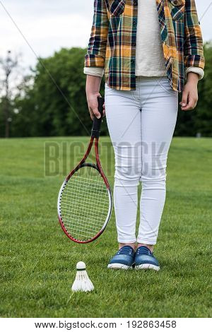 Cropped Shot Of Little Girl Holding Badminton Racquet And Standing On Green Grass With Shuttlecock