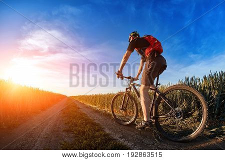 Cyclist in the helmet riding mountain bicyclist on outdoor trail against sunrise. Young sportsman dressed in the black sportwear and sporty shoes, with backpack. Beautiful sky with clouds like a background. Concept of the healthy lifestyle.