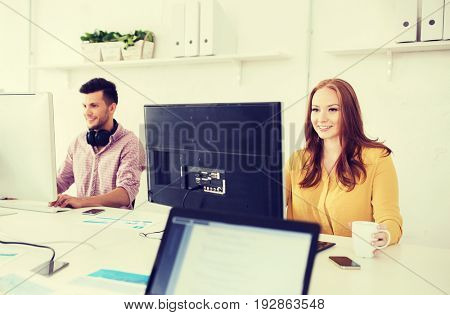 business, startup and people concept - happy creative team with computers working at office