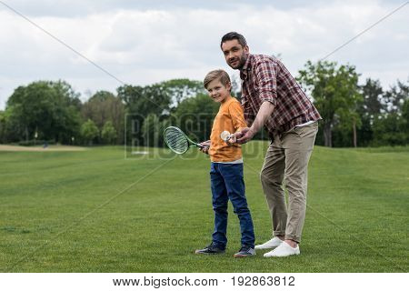 Father Holding Shuttlecock And Teaching Little Son Playing Badminton Outdoors