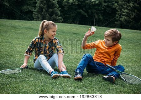 Adorable Little Kids With Badminton Rackets And Shuttlecock Sitting On The Grass At Park