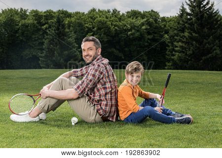 Happy Father And Son With Badminton Racquets Sitting On Grass And Smiling At Camera