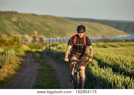 Young cyclist rides mountain bicyclist on the road in the field in the countryside. Sportsman dressed in the black sportwear, with helmet and backpack. Beautiful landscape with river like a background. Concept of the healthy lifestyle.