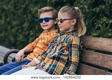 Stylish Little Kids In Sunglasses Sitting On Bench At Park