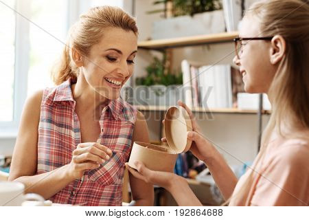 Best surprise. Cheerful loving daughter handing a box of a delicious confection to her dear mother being happy to receive it