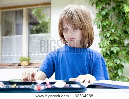 Boy with Blond Drawing a Picture Outdoors