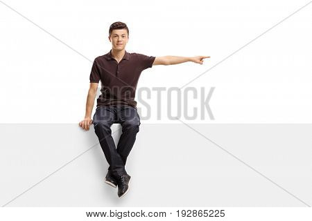 Teenage boy sitting on a panel and pointing right isolated on white background