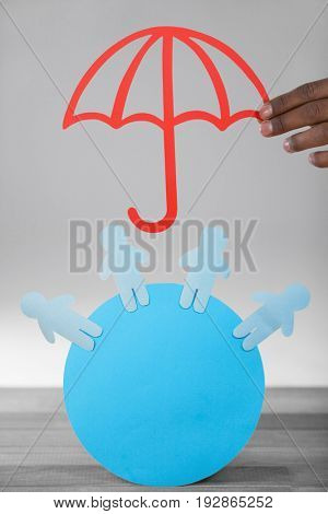 hand holding a red umbrella against blue paper cut out figures on circle