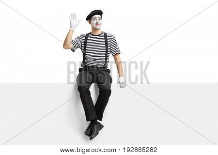 Mime artist sitting on a panel and waving at the camera isolated on white background