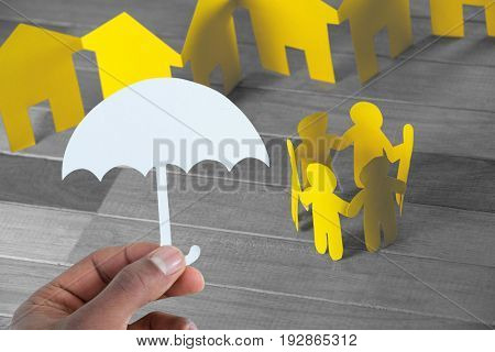hand holding an umbrella in paper against paper figures and houses on wooden table