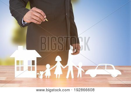 underwriter drawing a family against trees against clear blue sky on sunny day