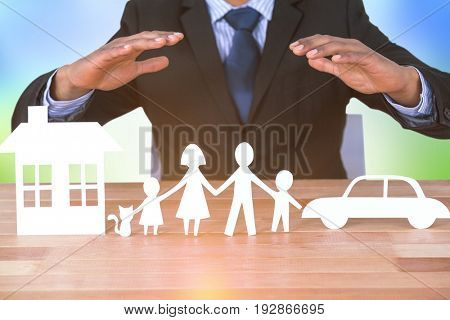 underwriter protecting family in paper with his hands against grass under a sunny sky
