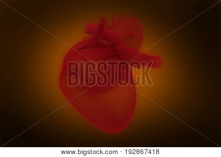 Digitally generated image of 3d human heart against orange background with vignette