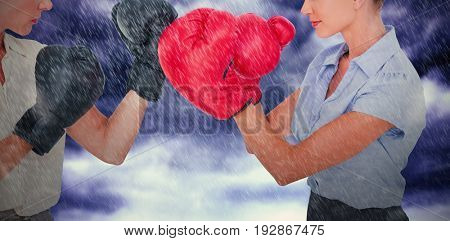 Businesswomen with boxing gloves fighting against gloomy sky