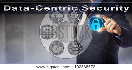 Blue chip information manager is plugging a locked virtual padlock into an interactive control interface. Information technology concept for Data-Centric Security and constant information monitoring.