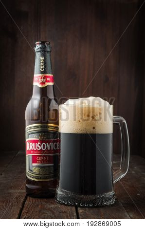 MINSK, BELARUS - APRIL 7, 2017: Krusovice dark royal beer on dark wooden background. Royal Brewery of Krusovice was founded in 1581. In 2007 it was acquired by Heineken.