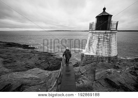 A man walks down a path towards Castle Hill Lighthouse in Rhode Island, black and white