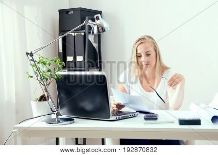Blonde Architect Is Reading Documents At Her Office
