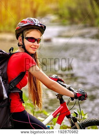 Woman traveling bicycle in summer park. Early morning with first rays of sun and fog. Cycling girl with with big backpack overcomes river. Sport trip is good for health. Trip on ecological route.