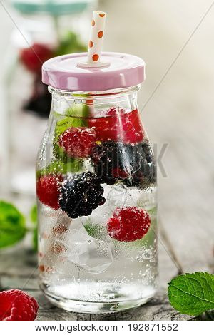 Healthy tasty fresh refreshing detox water in bottles or jars with raspberry blackberry mint and ice on wooden background. Closeup. Healthy Life Concept.