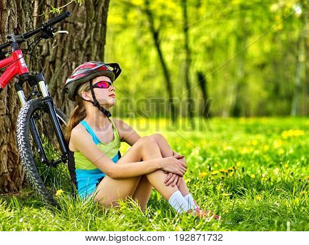 Woman traveling bicycle in summer park. Bicyclist girl watch on smart watch. Girl counts pulse after sport training. Girl hugs herself by knees is dreaming, looking sky. Trip on ecological route.