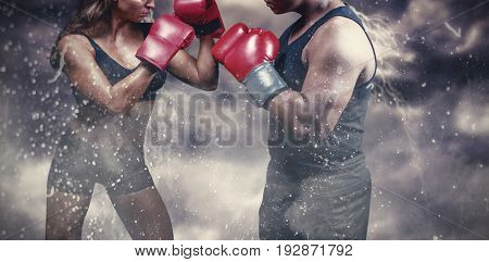 Male and female boxer with fighting stance against digitally generated image of color powder