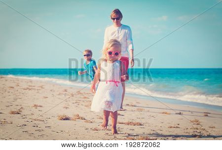 father with little son and daughter play on tropical beach