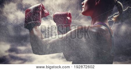 Side view of female boxer with fighting stance against splashing of yellow color powder
