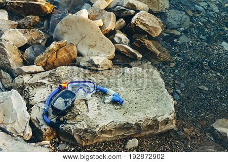 Blue Masks For Diving And Tubes Lie On The Beach On The Rocks. Tourism And Travel Concept
