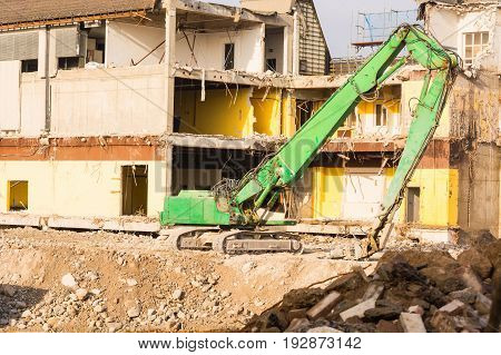 Excavator in front of a demolition site