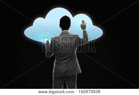business, people, cyberspace, computing and technology concept - businessman working with virtual cloud projection from back over black background