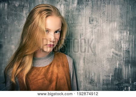 Portrait of a cute blonde girl teenager standing by a grunge wall.