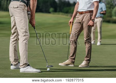 Cropped Shot Of Sportsmen Playing Golf Together On Golf Course At Daytime