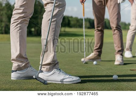 cropped shot of professional golf players getting ready to shot a ball