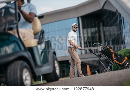 smiling man looking at camera while rolling golf bag with golf clubs in it