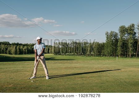 Full Length View Of Man In Cap Holding Golf Club And Hitting Ball On Green Lawn