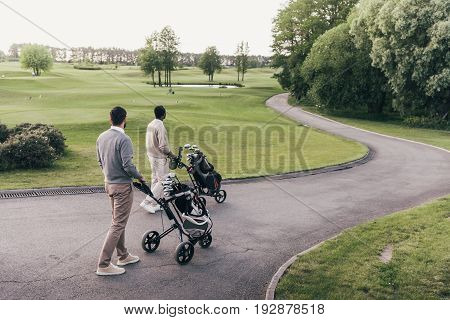 Back View Of Two Men Carrying Golf Clubs In Golf Bags And Walking At Golf Course