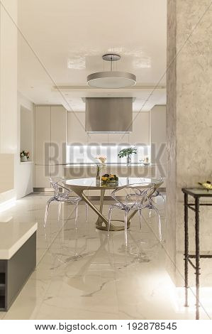 White modern kitchen with a tiled floor. There is a kitchen island with a hood, lockers with backlight, fancy table with glass chairs, plants in vases, fruit on the plate, hanging round lamp. Indoors. poster