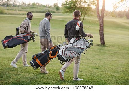 Multiethnic Golf Players With Golf Clubs In Bags Walking On Golf Course