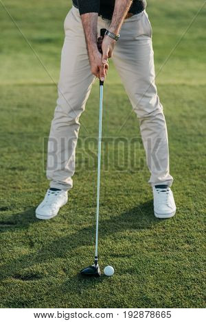 cropped view of stylish man playing golf on golf course at daytime