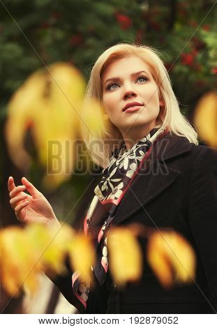 Happy young fashion blond woman walking in city park. Stylish female model in black coat outdoor